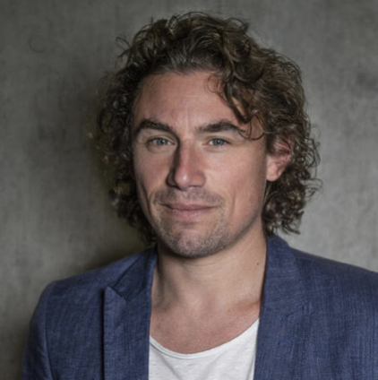 Smiling Frenchman with dark blond curly hair in a white crew neck shirt with a gray-blue blazer in front of a medium gray textured background