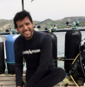 smiling Colombian man with dark hair and a moustache in a black wet suit on a doc