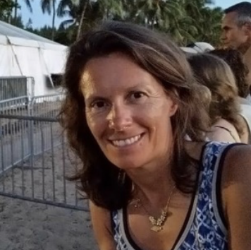 Smiling middle aged white women with shoulder length brown hair standing outside in a dark blue pattern tank top
