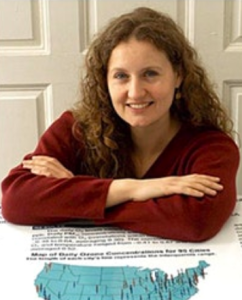 Smiling white woman with long curly auburn hair wearing a red sweater with her arms folded leaning over a table with a map of the usA